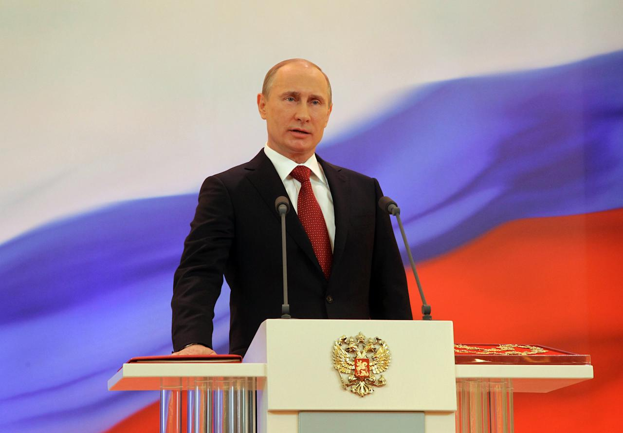 Vladimir Putin speaks with his hand on the Constitution during his inauguration ceremony as new Russia's president in Moscow Monday, May 7, 2012. Putin has been sworn in as Russia's president for a third term after four years as prime minister. (AP Photo/RIA Novosti Kremlin, Vladimir Rodionov, Presidential Press Service)