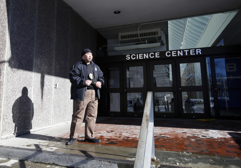 A security officer guards an entrance at the Science Center at Harvard University in Cambridge, Mass., Monday, Dec. 16, 2013. Four buildings on campus were evacuated Monday after campus police received an unconfirmed report that explosives may have been placed inside, interrupting final exams. (AP Photo/Elise Amendola)