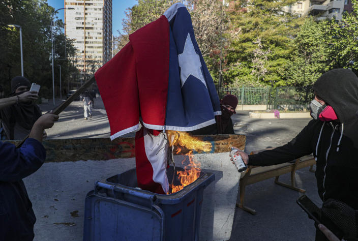 Demonstrators burn a Chilean flag during a protest against police in reaction to a video that appears to show an officer pushing a youth off a bridge the previous day at a protest, in Santiago, Chile, Saturday, Oct. 3, 2020. (AP Photo/Esteban Felix)