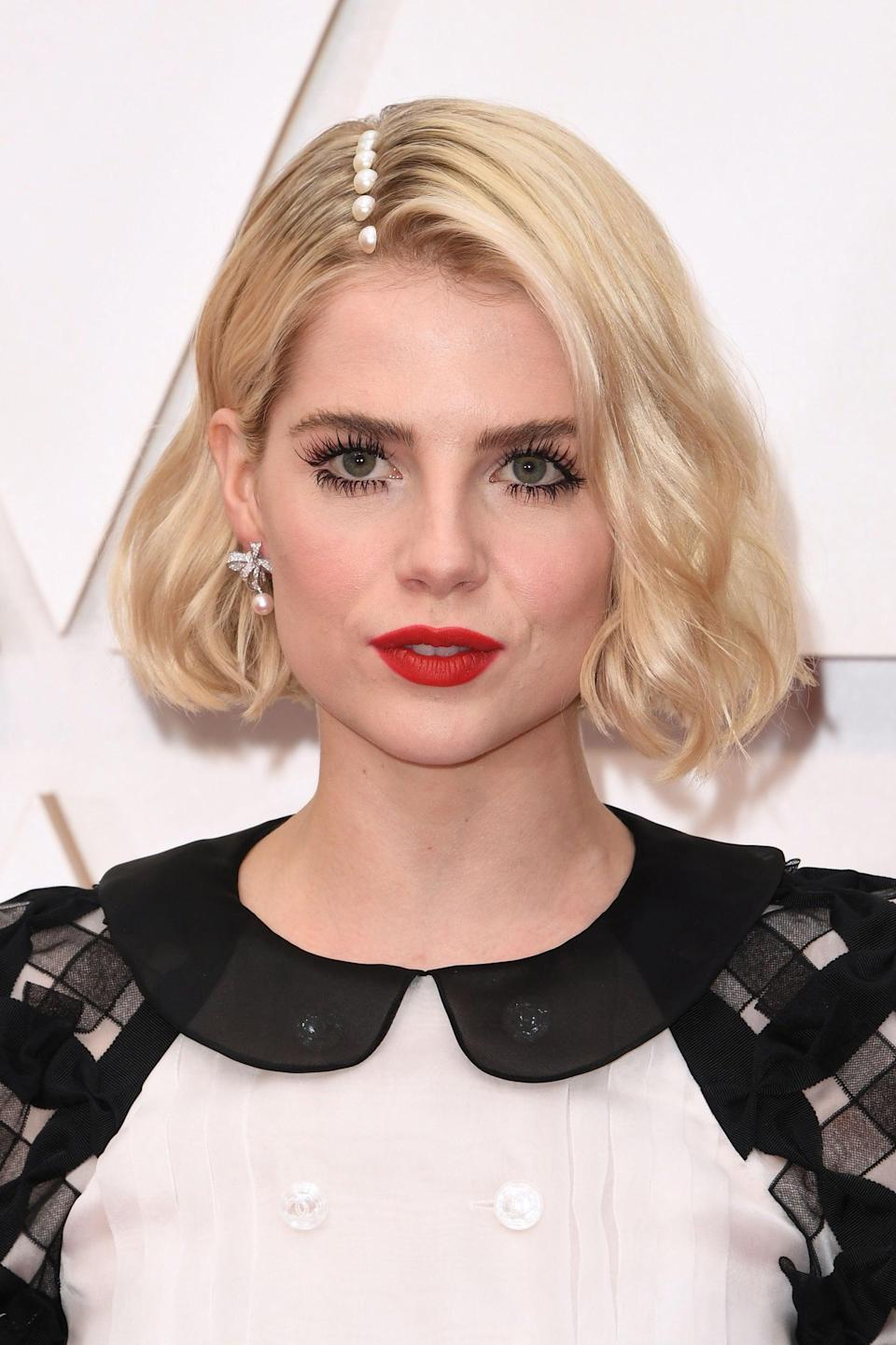 """Jenny Cho styled Lucy Boynton's side-parted bob with chunky pearls along her part — easily one of our favorite looks of the night.<span class=""""copyright"""">Photo: ROBYN BECK/AFP/Getty Images.</span>"""