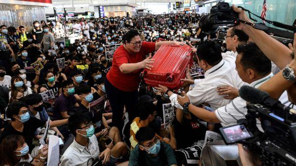 PHOTO: A tourist gives her luggage to security guards as she tries to enter the departures gate during another demonstration by protesters at Hong Kong's International Airport on Aug. 13, 2019. (Philip Fong/AFP/Getty Images)