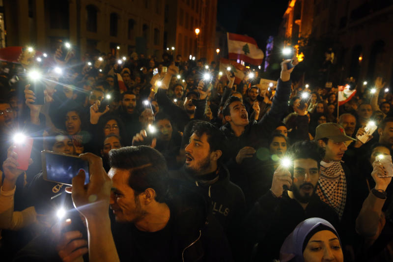Anti-government demonstrators chant slogans as they light up their mobile phones during a protest at a road leading to the parliament building in Beirut, Lebanon, Thursday, Jan. 16, 2020. Lebanese protesters Thursday decried security forces' use of violence during rallies over the past two days, including attacks on journalists and the detention of over 100 people. (AP Photo/Bilal Hussein)