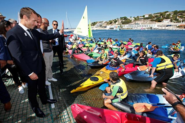 "French President Emmanuel Macron waves as he visits the site of the future Olympic Sailing venue (Voile Olympique) at the ""Marina Olympique"" nautical base in Marseille, France, after the decision for Paris to host of the 2024 Summer Olympics Games, September 21, 2017. REUTERS/Jean-Paul Pelissier"