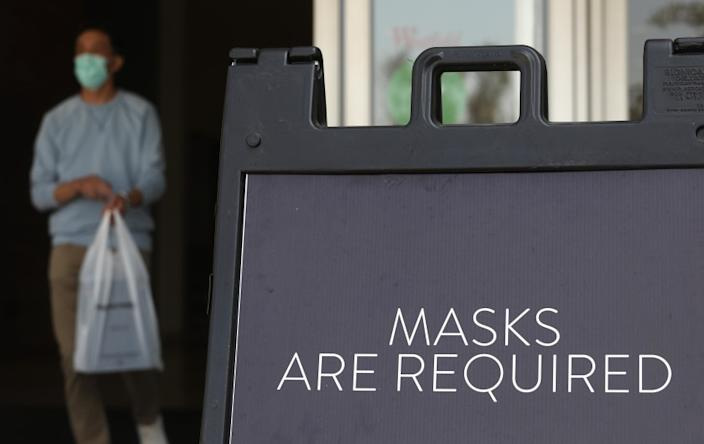 ARCADIA, CA - OCTOBER 07, 2020 - A sign tells customers to wear masks to prevent the spread of COVID-19 as shoppers return to indoor shopping at the Westfield Santa Anita shopping mall in Arcadia on October 7, 2020. This is the first day customers were allowed to return to indoor shopping after Los Angeles County eased restrictions and have reopened the malls and the individual stores. Such stores have been closed for weeks, but reopened Wednesday at 25% capacity. Westfield Santa Anita has placed Covid-related signage with one-way traffic, 6 feet distancing when waiting to get into individual stores, hand sanitizing stations and mask are required before entering the mall. (Genaro Molina / Los Angeles Times)