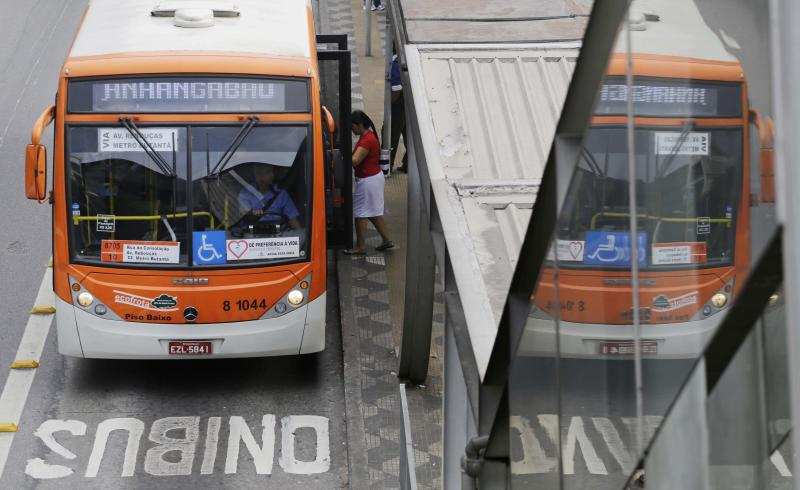 A woman boards a bus at a bus stop in Sao Paulo, Brazil, Thursday, June 20, 2013. Leaders in Brazil's two biggest cities said Wednesday that they reversed an increase in bus and subway fares that ignited anti-government protests that have spread across the nation in the past week. (AP Photo/Nelson Antoine)