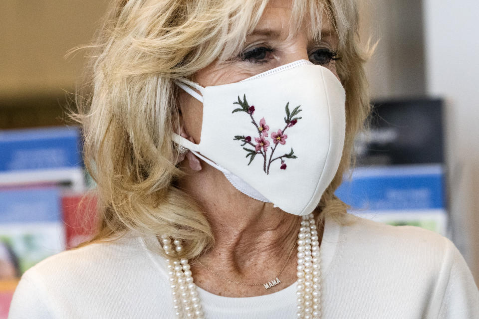 """First lady Jill Biden's necklace says """"Mama,"""" as she takes a tour of Whitman-Walker Health, Friday, Jan. 22, 2021, in Washington. (AP Photo/Jacquelyn Martin, Pool)"""