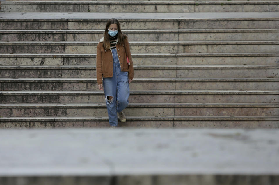A young woman wearing a face mask enters a subway station in Lisbon, Friday, Jan. 22, 2021. Portugal's COVID-19 surge is continuing unabated, with a new record of daily deaths, hospitalizations and patients in intensive care. (AP Photo/Armando Franca)