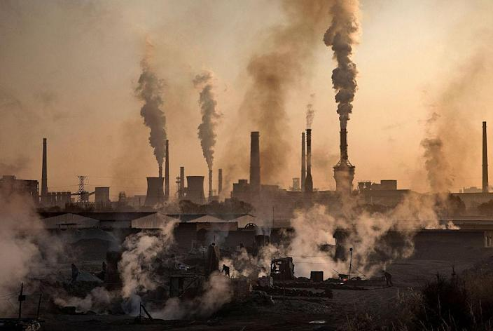 """Smoke billows from a large steel plant as a Chinese labourer works at an unauthorized steel factory, foreground, on November 4, 2016 in Inner Mongolia, China.<span class=""""copyright"""">Kevin Frayer/Getty Images</span>"""