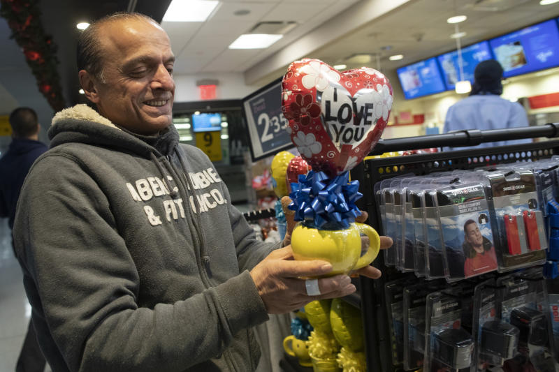 In this Tuesday, Dec. 3, 2019, photo, Mohammed Hafar buys a gift for his daughter Jana Hafar while waiting for her flight at JFK Airport in New York. Jana had been forced by President Donald Trump's travel ban to stay behind in Syria for months while her father, his wife and son Karim started rebuilding their lives in Bloomfield, N.J., with no clear idea of when the family would be together again. Mohammed was part of a federal lawsuit filed in August of this year over the travel ban waiver process. (AP Photo/Mary Altaffer)