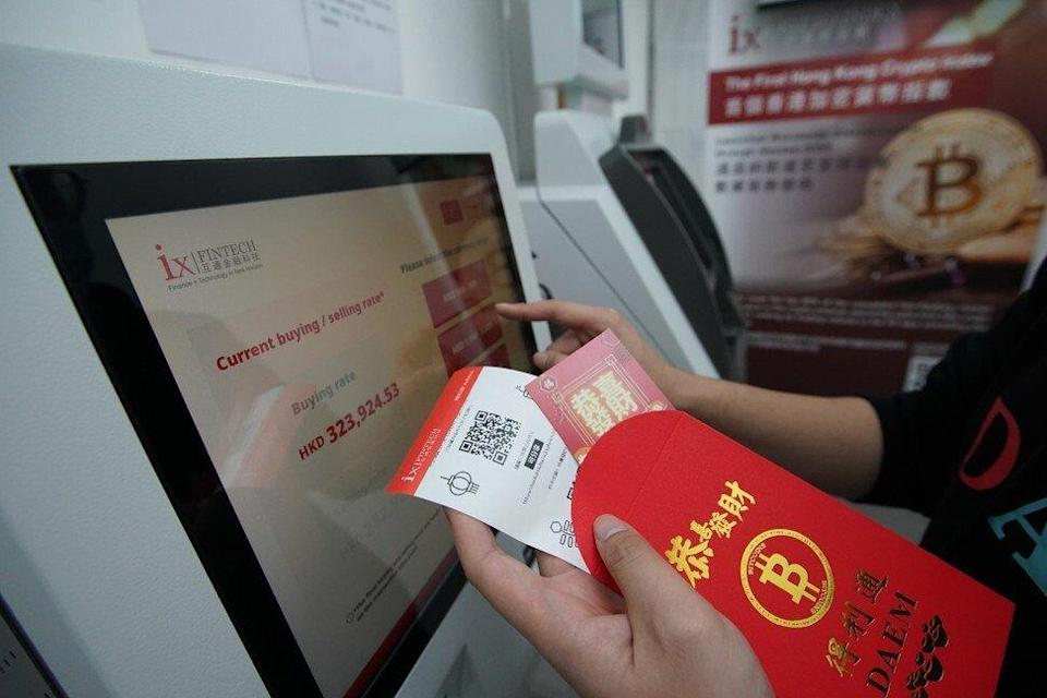 A manager of ixFintech demonstrates how to use the paper wallet and QR code to buy bitcoin. Photo: SCMP