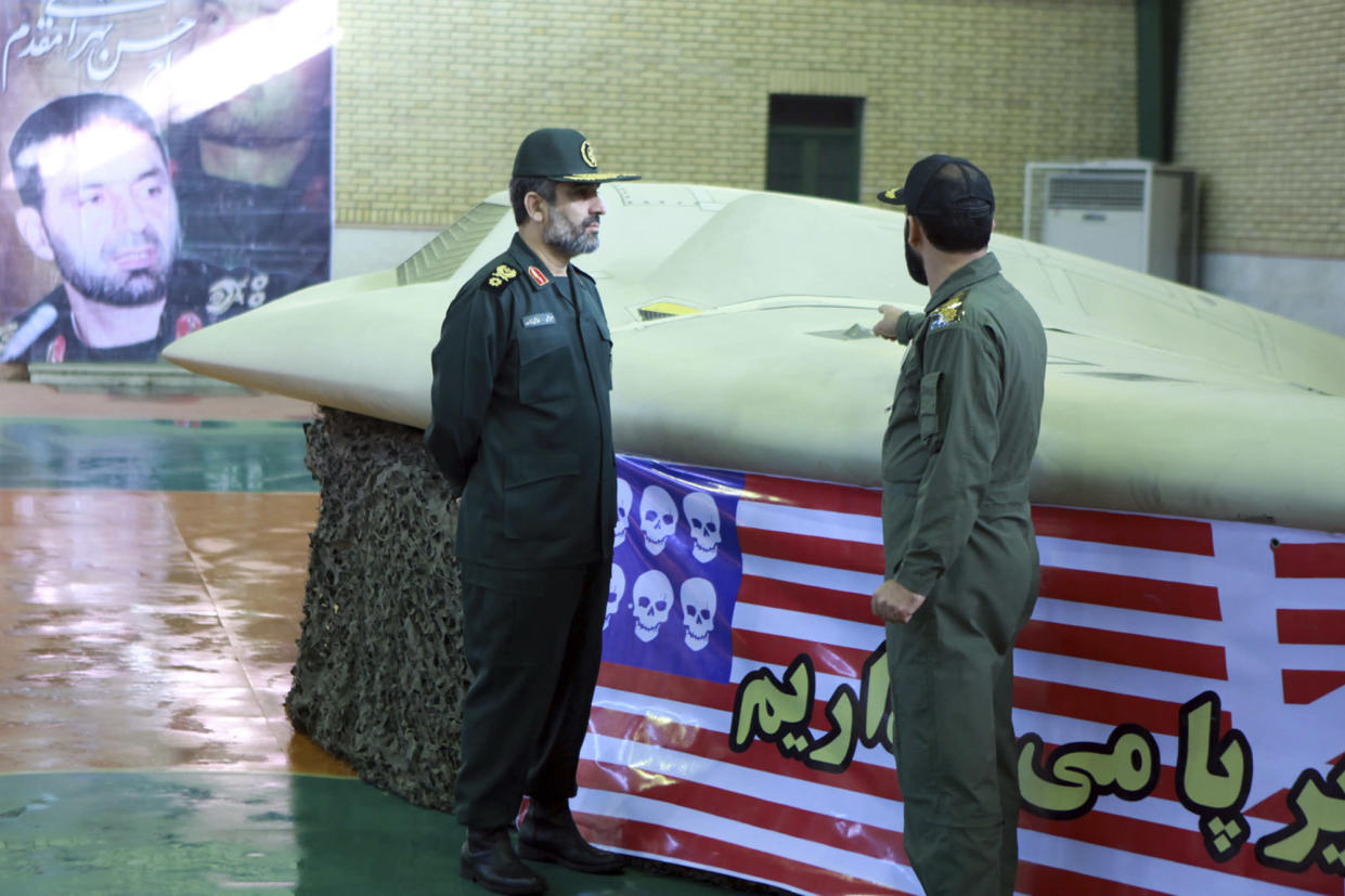 A photo released by Iran in 2011 purports to show Gen. Amir Ali Hajizadeh, left, the chief of the aerospace division of the Iran Revolutionary Guard Corps, listening to an unidentified colonel as he points to a downed U.S. RQ-170 Sentinel drone. (Photo: Sepahnews/AP)