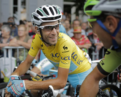 Italy's Vincenzo Nibali, wearing the overall leader's yellow jersey, talks to Slovenia's Kristjian Koren, right, prior to the start of the nineteenth stage of the Tour de France cycling race over 208.5 kilometers (129.6 miles) with start in Maubourguet and finish in Bergerac, France, Friday, July 25, 2014. (AP Photo/Laurent Cipriani)