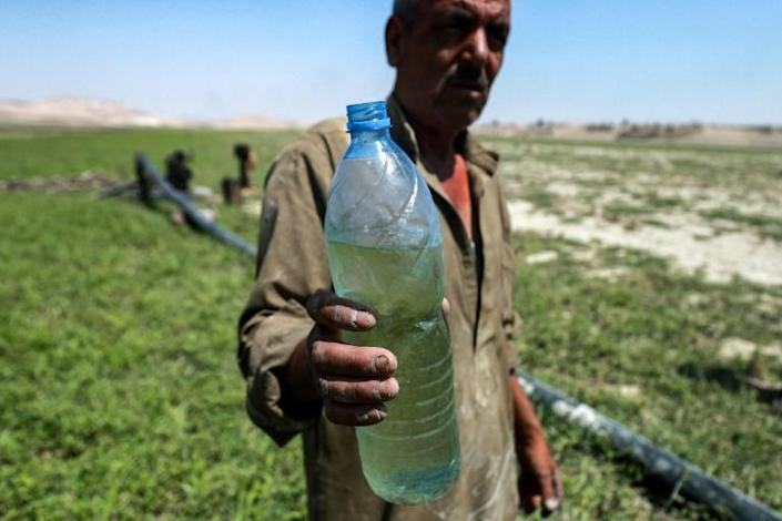 A man holding a water bottle stands near a pump drawing water from the shallows of the Lake Assad reservoir, along the Euphrates river by the town of Rumayleh in eastern Syria (AFP/Delil SOULEIMAN)