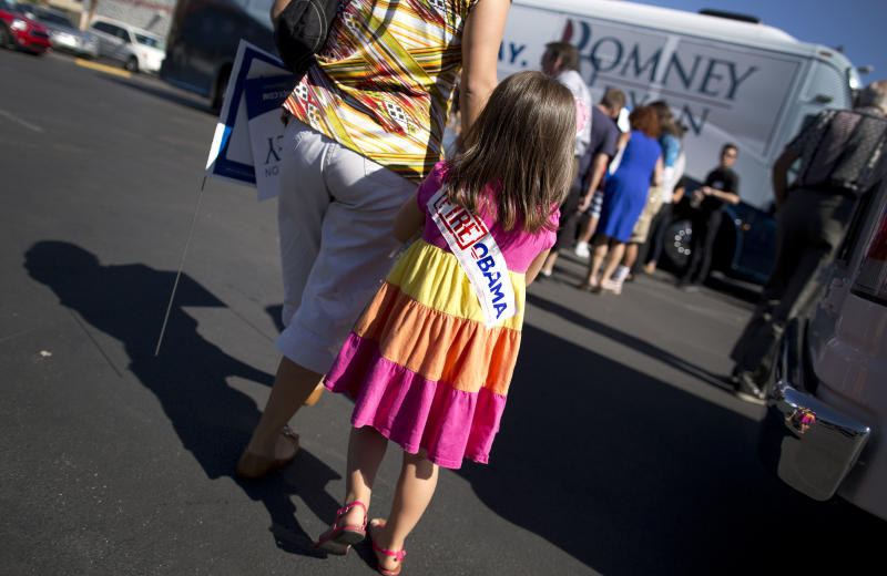 Alyta Mejia leads her daughter, Viky Kivisels, 4, back to their car after listening to comedian Paul Rodriguez speak at a rally for Mitt Romney, Saturday, Oct. 20, 2012, in Las Vegas. Romney officials argue that Hispanics, who suffer from a 9.9 percent unemployment rate, more than 2 points higher than the national rate, are naturally drawn to the GOP ticket. But some Romney supporters are pessimistic that Republicans can make inroads with a population that, many polls show, favors Obama by a 2-1 margin. (AP Photo/Julie Jacobson)