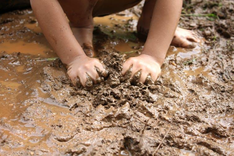 A child's hands playing with mud in a puddle.