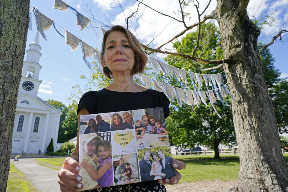Widow Marcy Jacobs holds family photos as she stands under flags with names of people, including her husband, Keith Jacobs, who have died from COVID-19, outside the First Congressional Church, Thursday, June 17, 2021, in Holliston, Mass. The flags are part of the COVID Art and Remembrance project spearheaded by Marcy's daughter, Jaclyn Winer. (AP Photo/Elise Amendola)