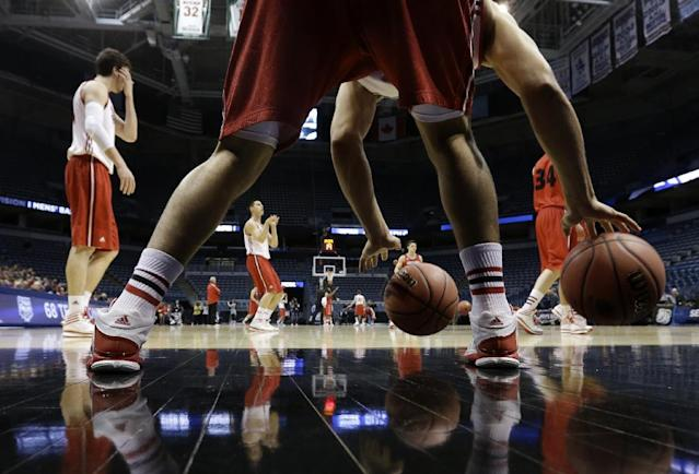 Wisconsin guard Traevon Jackson dribbles two balls as players warm up during a practice session for their NCAA college basketball tournament game Wednesday, March 19, 2014, in Milwaukee. Wisconsin plays American on Thursday, March 20, 2014. (AP Photo/Morry Gash)