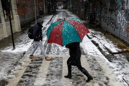 A woman walks in the snow during a winter nor'easter storm in the Chinatown area of New York City, U.S., March 21, 2018. REUTERS/Brendan McDermid