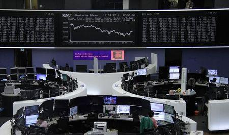 Traders work at their desks in front of the German share price index, DAX board, at the stock exchange in Frankfurt, Germany, March 16, 2017. REUTERS/Staff/Remote