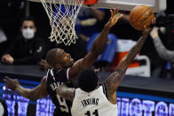 Brooklyn Nets guard Kyrie Irving, right, shoots as Los Angeles Clippers center Serge Ibaka defends during the first half of an NBA basketball game Sunday, Feb. 21, 2021, in Los Angeles. (AP Photo/Mark J. Terrill)