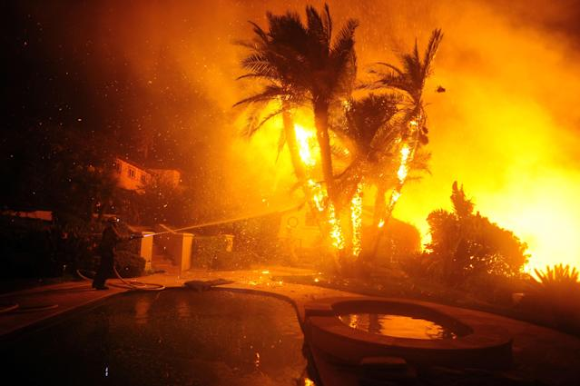 <p>A firefighter puts water on a palm tree in the back of a house on Rancho Vista Lane in Santa Paula, Calif., on Dec. 5, 2017. (Photo: Neal Waters via ZUMA Wire) </p>