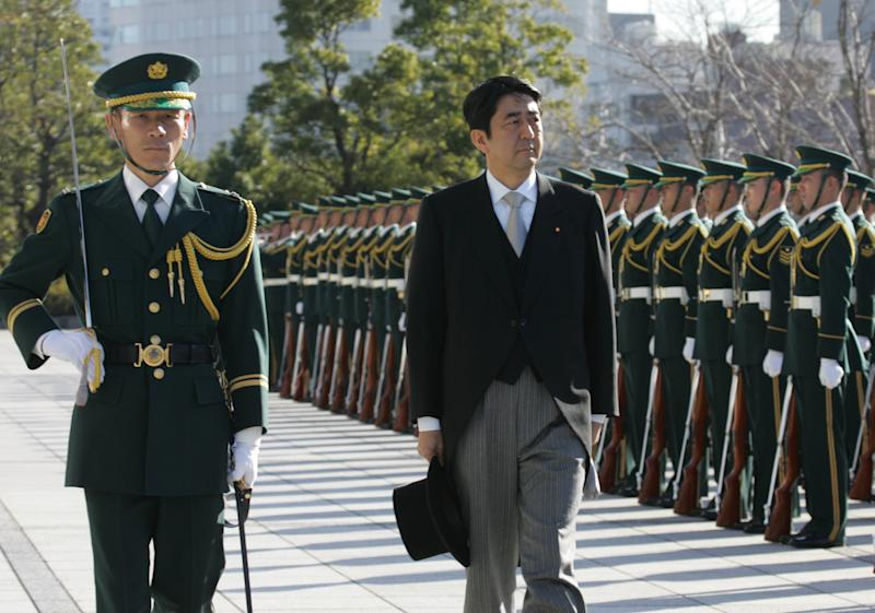 FILE - In this Jan. 9, 2007 file photo, Japanese Prime Minister Shinzo Abe, right, reviews an honor guard in a ceremony at the Defense Ministry in Tokyo on the day Japan's conservative government upgraded the Defense Agency to a full ministry for the first time since World War II, in line with Abe's push to give the military a greater profile. Japan's military is kept on a very short leash under a war-renouncing constitution written by U.S. officials whose main concern was keeping Japan from rearming soon after World War II. But if Japan's soon-to-be prime minister Abe, who set to take office for a second time after leading his Liberal Democratic Party to victory in elections last Sunday, Dec. 16, 2012, has his way, the status quo may be in for some change. (AP Photo/Katsumi Kasahara, File)