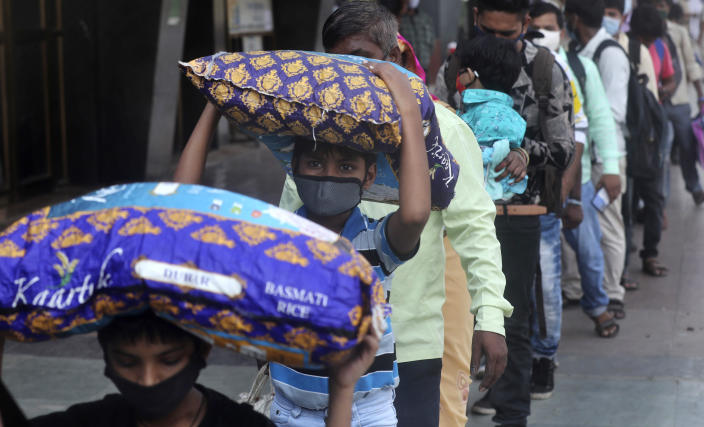 People wearing masks as a precaution against the coronavirus stand in a queue to board trains at Lokmanya Tilak Terminus in Mumbai, India, Monday, April 12, 2021. With its explosive surge in recent days, India's confirmed infections surpassed Brazil's total Monday as the second-worst hit country. (AP Photo/Rafiq Maqbool)