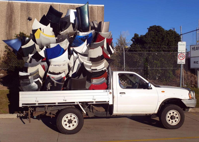 A white ute piled high with bumpers in the tray.