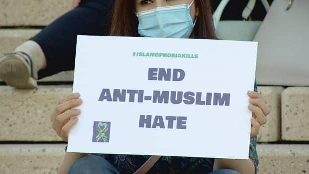 An attendee at the anti-hate rally Friday night holds up a sign. The rally comes after a series of hate-motivated attacks against Muslim women in Alberta. (Jamie McCannell/CBC - image credit)