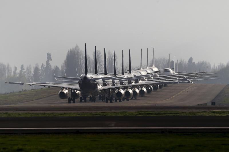 Planes are parked next to a landing track at the international airport of Santiago city