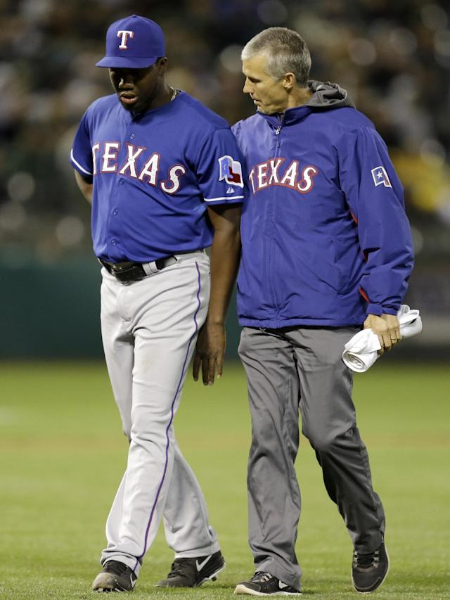 Texas Rangers' Pedro Figueroa, left, is walked off the field by trainer Kevin Harmon after hitting Oakland Athletics' Josh Reddick with a pitch in the eighth inning of a baseball game Tuesday, April 22, 2014, in Oakland, Calif. (AP Photo/Ben Margot)