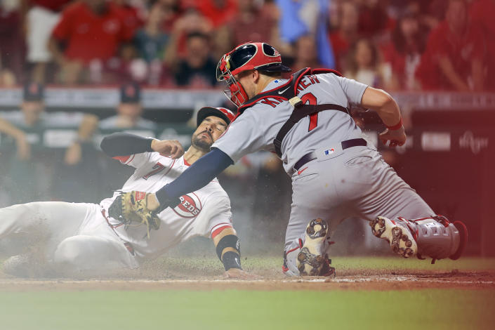 Cincinnati Reds' Eugenio Suarez, left, is out at home plate as St. Louis Cardinals' Andrew Knizner, right, tags him during the seventh inning of a baseball game in Cincinnati, Friday, July 23, 2021. (AP Photo/Aaron Doster)