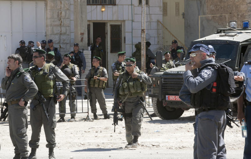 Israeli security forces surround a house illegally occupied by Jewish settlers in the West Bank city of Hebron, Wednesday, April 4, 2012. Israeli security forces began evicting dozens of settlers Wednesday from a building they illegally took over and lived in without the required military approval in Hebron, police said.(AP Photo/Sebastian Scheiner)