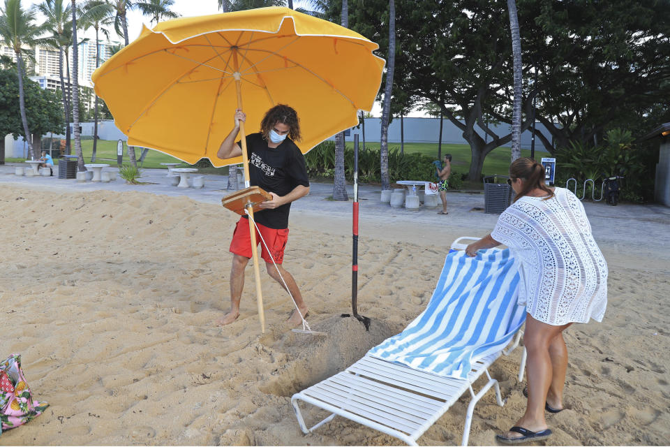 Mitch Kemp, left, a worker at a Waikiki Beach rental company, sets up an umbrella for visitor Leena Kilman on Waikiki Beach, Thursday, Oct. 15, 2020, in Honolulu. Kilman, who is visiting from New Hampshire, spent two weeks in mandatory quarantine and Thursday was her first day to visit the beach. The beach rental company opened for the first time Thursday since closing in March due to the COVID-19 pandemic. Kilman was their first rental customer since closing. (AP Photo/Marco Garcia)