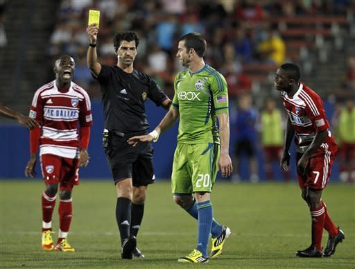 Referee Fotis Bazakos issues a yellow card to Seattle Sounders' Zach Scott (20) for sweeping FC Dallas's Fabian Castillo (7), as Jair Benitez (5) reacts to the play in the second half of an MLS soccer game Wednesday, May 9, 2012, in Frisco, Texas. The Sounders won 2-0. (AP Photo/Tony Gutierrez