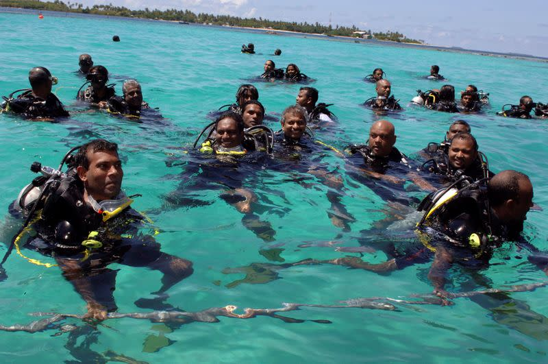 FILE PHOTO: Members of the Maldives government swim to attend the first underwater cabinet meeting in the Maldives