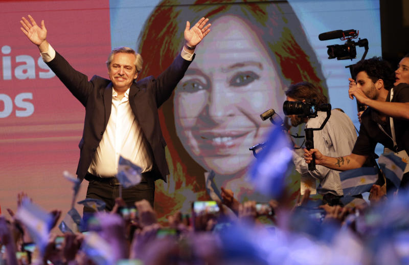 Peronist presidential candidate Alberto Fernández waves to supporters in front of a large image of his running mate, former President Cristina Fernández, after incumbent President Mauricio Macri conceded defeat at the end of election day in Buenos Aires, Argentina, Sunday, Oct. 27, 2019. (AP Photo/Daniel Jayo)