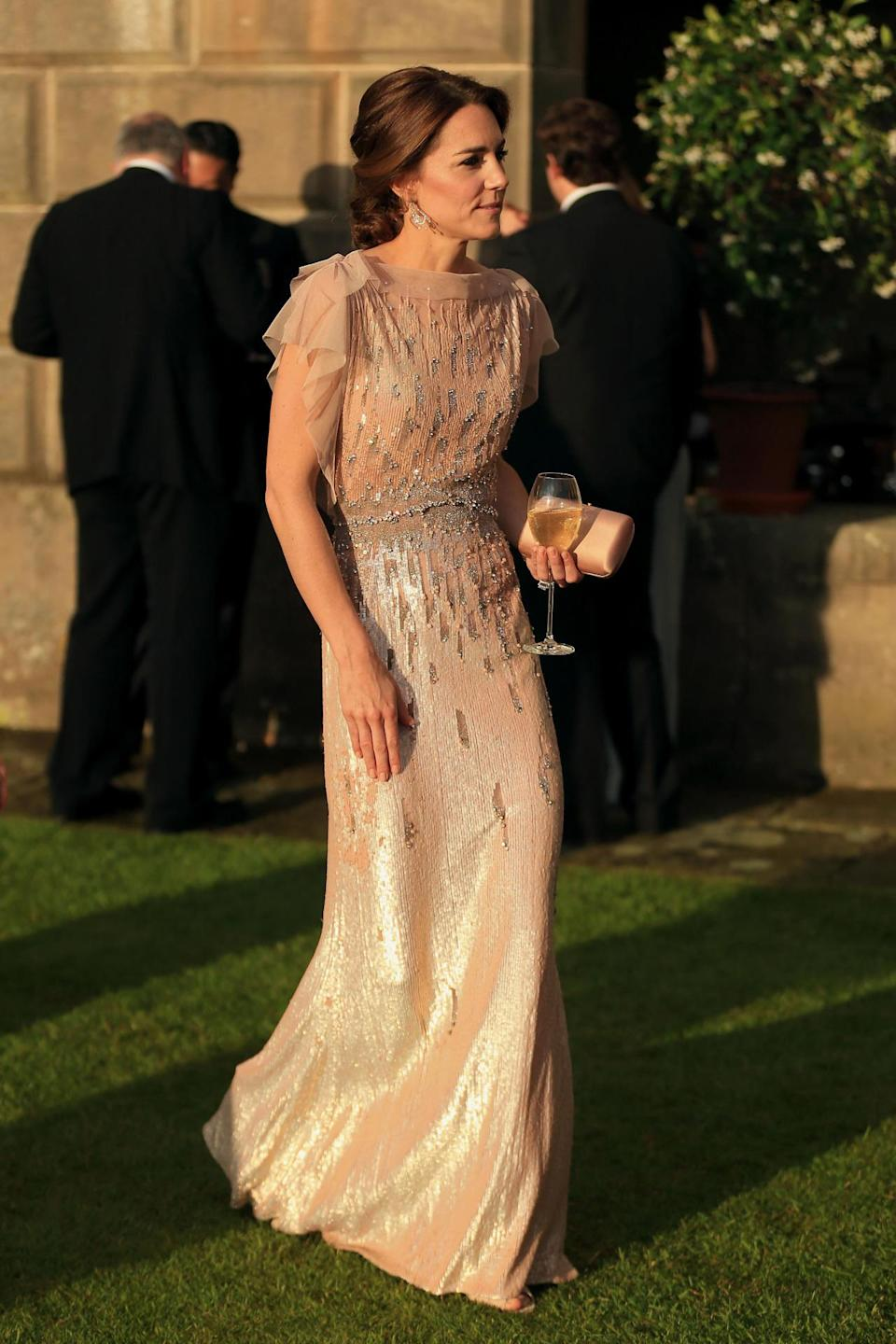 <p>Kate looked stunning in a champagne Jenny Packham gown for a gala dinner in Norfolk. Recycling a look she first wore in 2011, the Duchess's accessories included a dusky pink Prada clutch, L.K. Bennett sandals and diamond earrings loaned to her by the Queen.</p><p><i>[Photo: PA]</i></p>