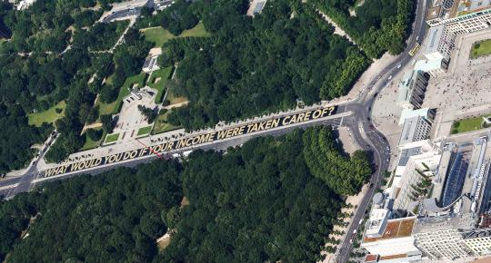 <p>A huge banner promoting the minimum guaranteed income proposal ahead of its vote is seen near the Brandenburg gate in Berlin, Germany, May 29, 2016. <em>(Reuters/Hannibal Hanschke)</em> </p>