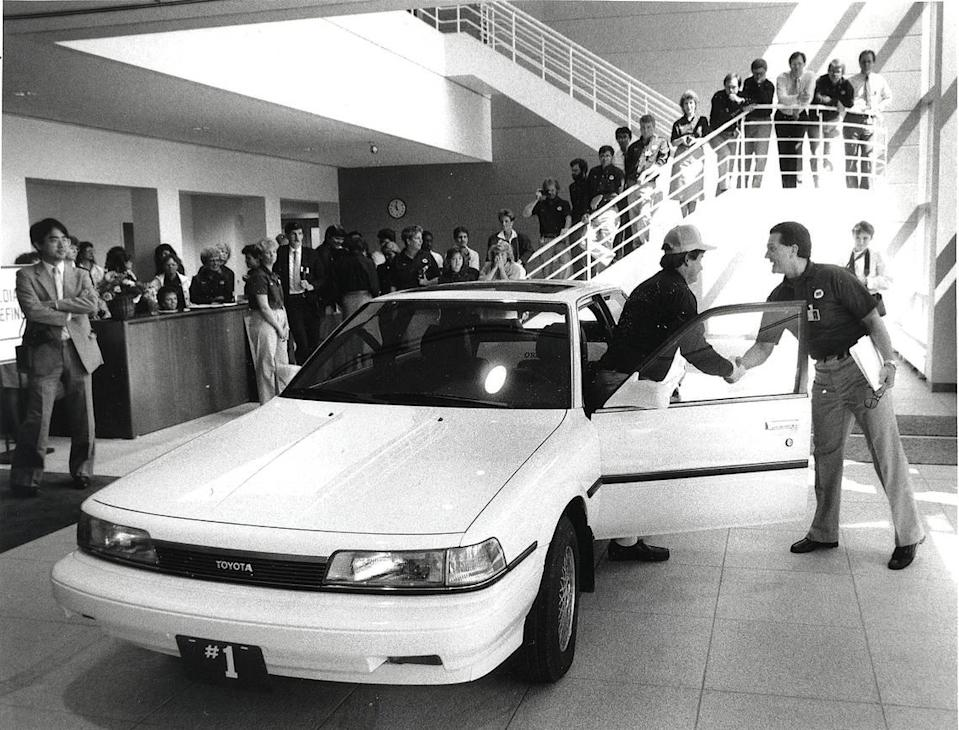The first Toyota Camry produced at the Georgetown, Kentucky Plant. Mike Dodge (right), the plant's general manager, shakes hands with Lee Pokriva of the plant's quality control unit after Pokriva drove the car into the lobby of the administration building. The car was put on permanent display at the plant on May 26, 1988. David Perry | Staff