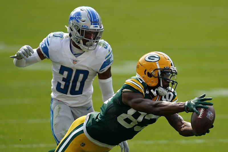 Green Bay Packers' Marquez Valdes-Scantling dives for a pass in front of Detroit Lions' Jeff Okudah during the second half at Lambeau Field on Sept. 20, 2020 in Green Bay, Wis.