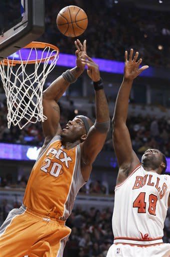 Phoenix Suns center Jermaine O'Neal, left, shoots past Chicago Bulls center Nazr Mohammed during the first half of an NBA basketball game in Chicago on Saturday, Jan. 12, 2013. (AP Photo/Nam Y. Huh)