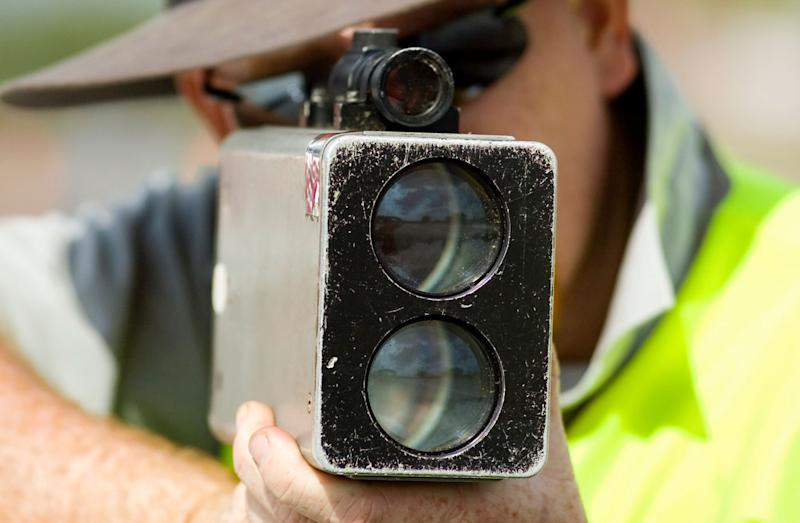 A man is pictured holding a speed camera.