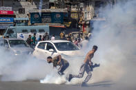 A Kashmiri Shiite Muslim run for cover as other prepare to throws back tear gas shell fired by Indian police during a religious procession in central Srinagar, Indian controlled Kashmir, Tuesday, Aug. 17, 2021.Police in Indian-controlled Kashmir on Tuesday fired tear gas and warning shots to disperse hundreds of Shiite Muslims, while detaining dozens who attempted to participate in processions marking the Muslim month of Muharram. (AP Photo/Dar Yasin)