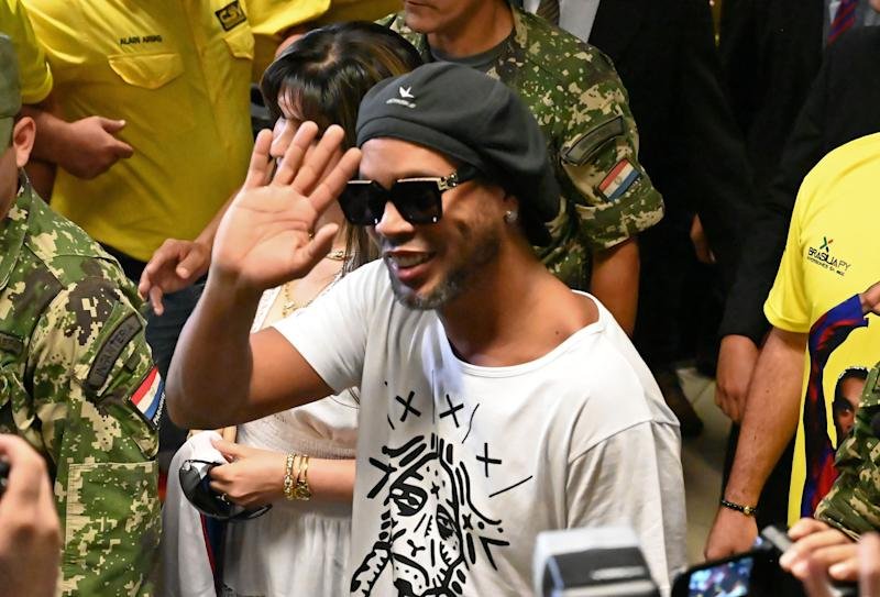"Brazilian ex-football star Ronaldinho Gaucho waves upon arriving at Silvio Pettirossi International Airport in Luque, near Asuncion, on March 4, 2020. - Ronaldinho arrived in Paraguay to present his latest book ""Genio en la Vida"" and a health programme for girls and boys. (Photo by Norberto DUARTE / AFP) (Photo by NORBERTO DUARTE/AFP via Getty Images)"