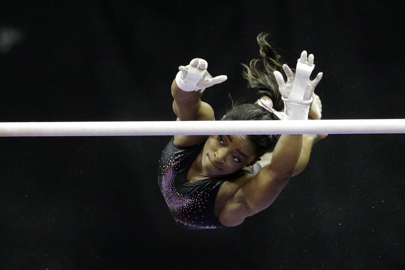 Simone Biles practices on the uneven bars for the senior women's competition at the 2019 U.S. Gymnastics Championships Sunday, Aug. 11, 2019, in Kansas City, Mo. (AP Photo/Charlie Riedel)