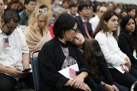 Immigrant Mika Toyoura, 51, attends a naturalization ceremony to become a new U.S. citizen with her daughter Lana Mingasson, 13, in Los Angeles, California, U.S., September 20, 2017. REUTERS/Lucy Nicholson