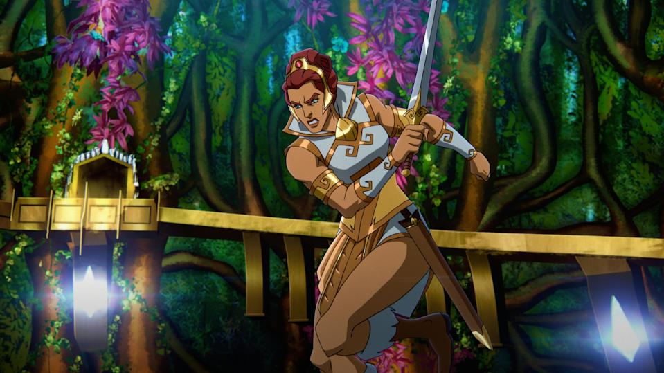 In a CG animated still from Masters of the Universe: Revelation, Teela, a light-skinned female with short auburn hair and light-colored eyes, lunges forward while holding her golden-hilted sword. She wears white and gold armor, a golden head piece with a red jewel in the center and brown boots with white fur trim. A wooden bridge reflects light at its base as it stretches between the trees in the forest visible behind her.