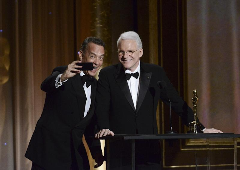 Actor Tom Hanks, left, takes a photo with actor and honoree Steve Martin at the 2013 Governors Awards on Saturday, Nov. 16, 2013 in Los Angeles. (Photo by Dan Steinberg/Invision/AP)