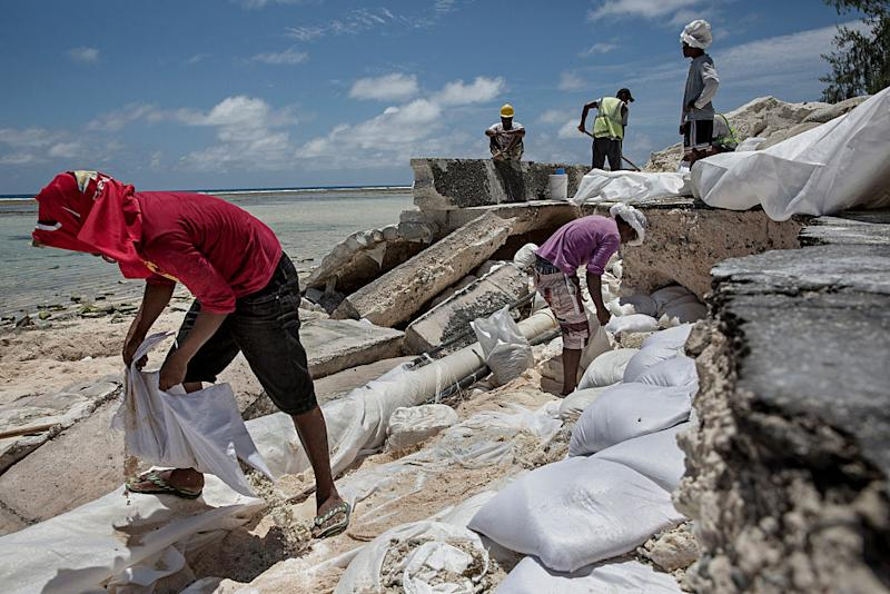 Damaged roads due to the flooding in Kirbati - Tarawa's single paved road has collapsed because of the flooding from the sea. The people of Kiribati are under pressure to relocate due to sea level rise. Each year, the sea level rises by about half an inch. Though this may not sound like much, it is a big deal considering the islands are only a few feet above sea level, which puts them at risk of flooding and sea swells. | Jonas Gratzer—LightRocket via Getty Images